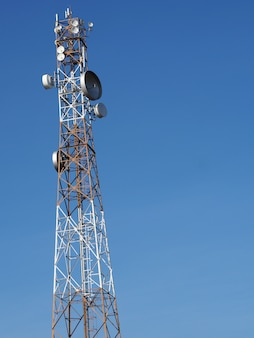 Communication tower with sun blue sky background