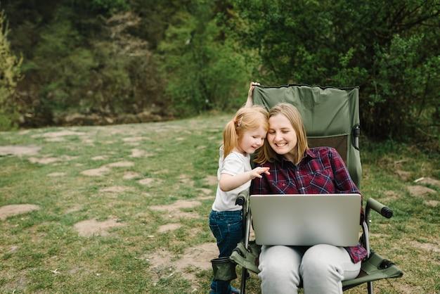 自然の中で火のそばのラップトップで家族とオンラインでコミュニケーション