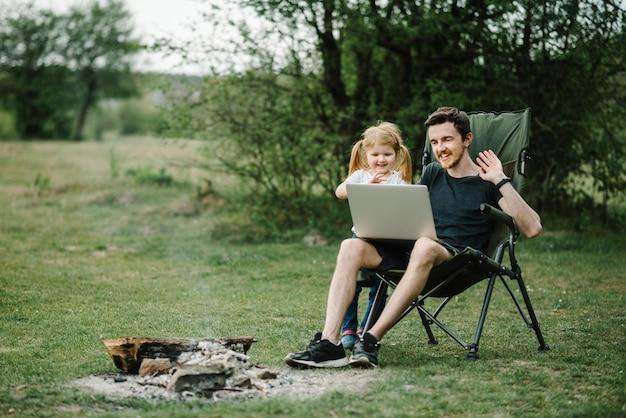 自然の中で火のそばのラップトップで家族とオンラインでコミュニケーション Premium写真