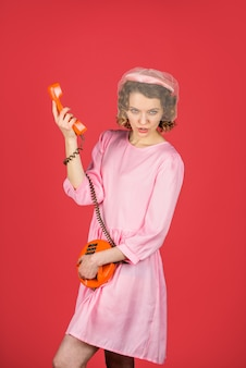 Communication woman talking on old phone woman in pink dress with telephone handset happy woman