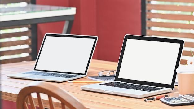 통신 작업 영역 테이블에 빈 화면이 두 장치 노트북 컴퓨터.