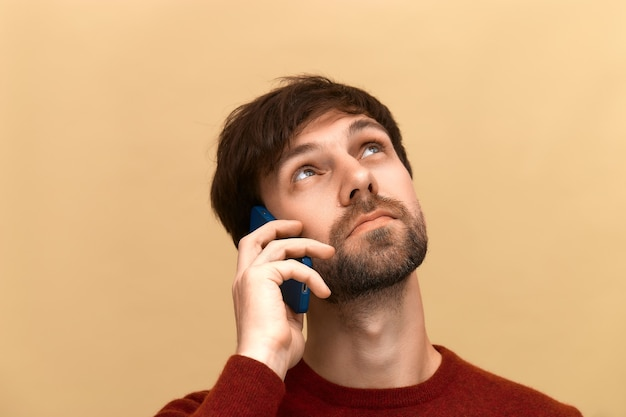 Communications. photo of young man with beard has phone conversation, holds mobile phone near ear, tells news to friend, focused away, wears sweater, posing against beige wall