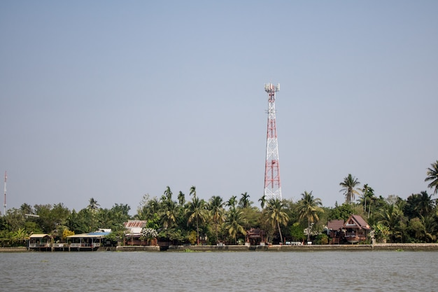 Communications tower in a village near the river with blue cloud sky background