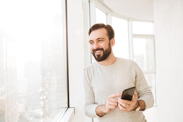 携帯電話でチャットまたはテキストメッセージを入力しながら、大きな窓から見ている白いシャツを着たコミュニケーションの人