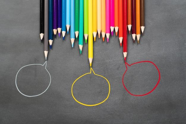 コミュニティコミュニケーションは、人々の会議、ソーシャルメディアの相互作用と関与を表します。コピースペースと黒い表面にアイデアを共有する鉛筆のグループ