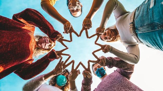 Сообщество смешанных молодых людей поддерживает друг друга в борьбе с коронавирусом - новая концепция нормального образа жизни друзей в маске на открытом воздухе.