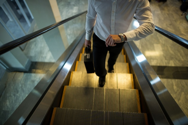 Pendolare che controlla il tempo mentre cammina sulla scala mobile
