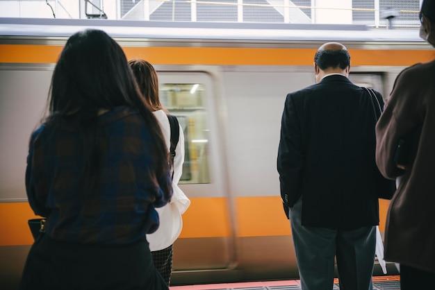 駅で緊張が止まるのを待っている通勤者