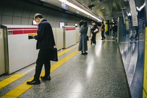 駅で地下鉄の電車を待っている通勤者