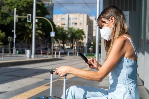 Поездка по городу во время новой нормальной жизни. женщина в защитной маске от вспышки коронавируса использует мобильный телефон в ожидании общественного транспорта.