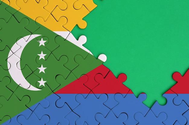 코모로 스 깃발은 오른쪽에 무료 녹색 복사 공간이있는 완성 된 직소 퍼즐에 그려져 있습니다.