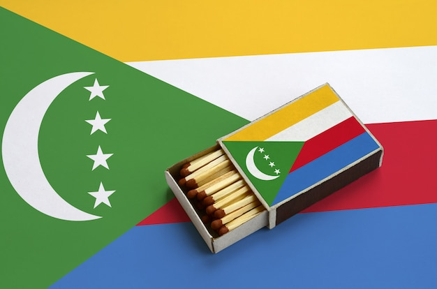 Comoros flag  is shown in an open matchbox, which is filled with matches and lies on a large flag