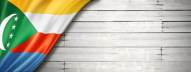 Флаг коморских островов на старой белой стене. горизонтальный панорамный баннер.