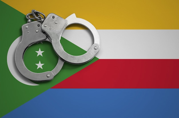 Comoros flag  and police handcuffs. the concept of crime and offenses in the country