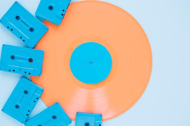 Компактные кассеты возле оранжевой виниловой пластинки