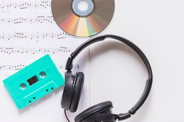 Compact disc; cassette and headphone on musical note over white background