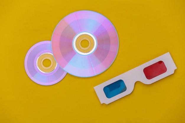 Компакт-диск с коробкой, 3d-очки на желтом фоне. вид сверху