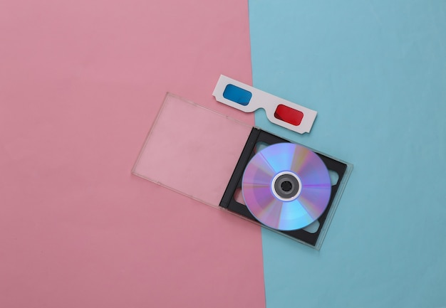 Compact disc with box, 3d glasses on pink blue pastel background. top view