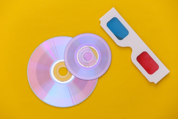 Compact disc with box, 3d glasses on yellow background. top view