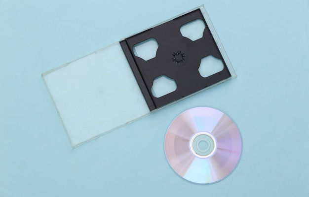 Compact disc with box on a blue background. top view, minimalism