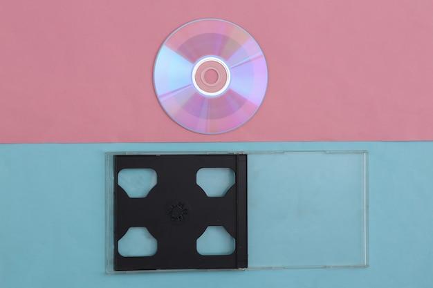 Компакт-диск с коробкой на розово-голубом пастельном фоне. вид сверху, минимализм