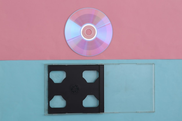 Compact disc with box on pink blue pastel background. top view, minimalism
