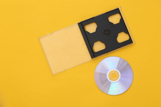 Compact disc with box on yellow background. top view, minimalism