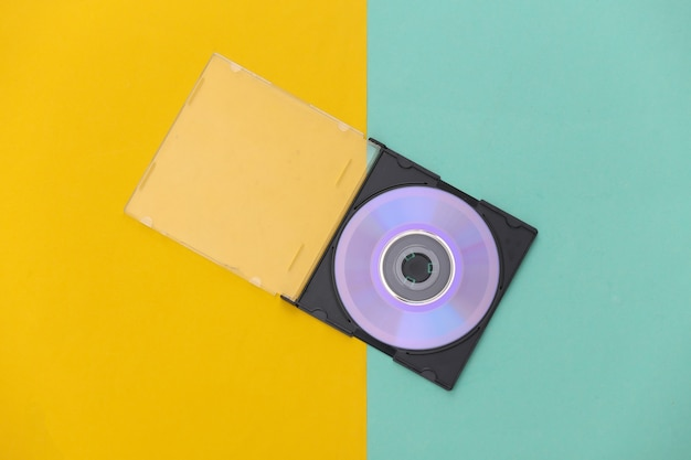 Compact disc with box on yellow blue background. top view, minimalism