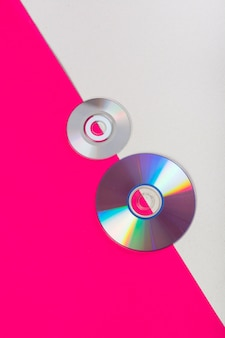 Compact discs on an pink and white dual backdrop