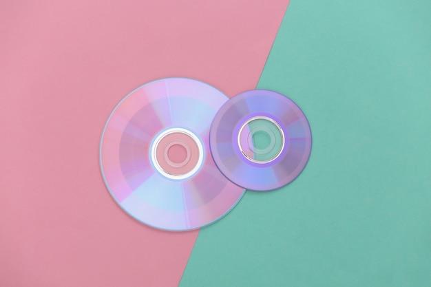 Компакт-диски на розово-голубом пастельном фоне. вид сверху