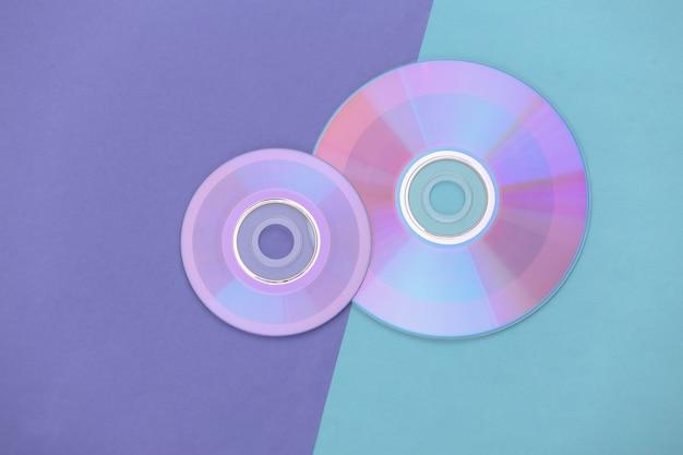 Компакт-диски на пурпурно-голубом пастельном фоне. вид сверху