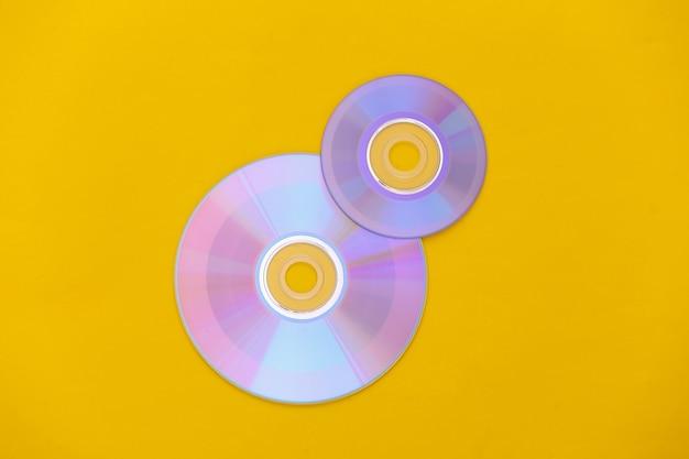 Компакт-диски на желтом фоне. вид сверху