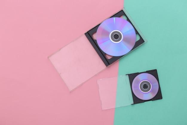 Компакт-диски с коробками на розово-голубом фоне. вид сверху