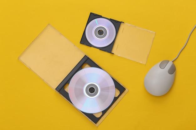 Компакт-диски с коробками, ретро компьютерная мышь на желтом фоне. вид сверху