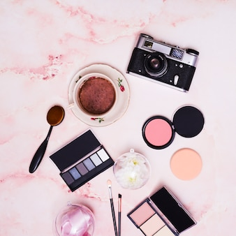 Compact face powder; ribbon; coffee cup; makeup brush; eyeshadow palette and vintage camera on pink textured backdrop