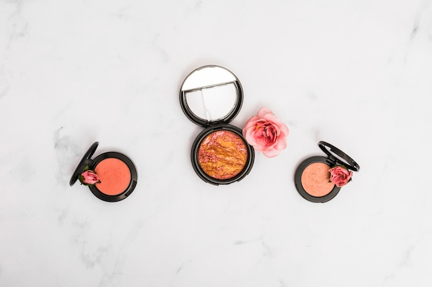 Compact face powder with rose and buds on marble textured backdrop