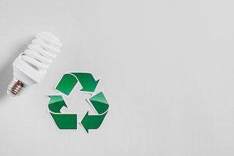 Compact fluorescent light bulb and recycle icon on white backdrop