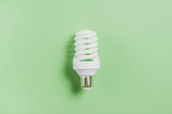 Compact fluorescent light bulb on green background