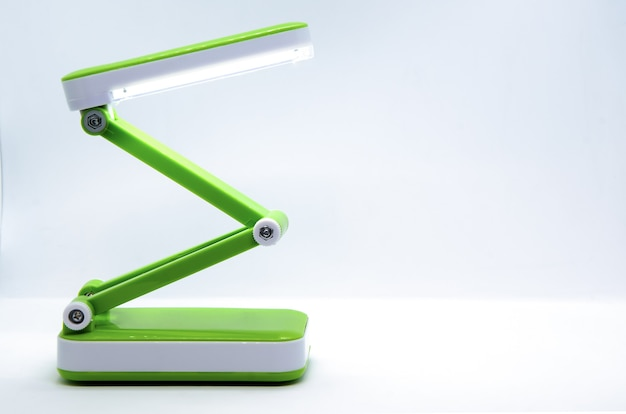 흰색에 밝은 녹색 플라스틱으로 만들어진 유연한 본체와 컴팩트 한 접이식 휴대용 led 데스크 램프.