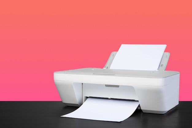 ピンクの背景に対してコンパクトな家庭用レーザープリンター
