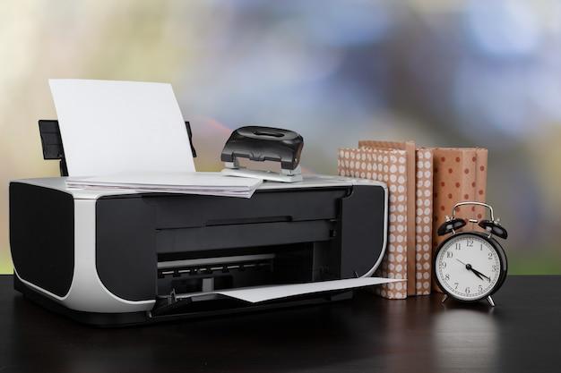 흐릿한 배경에 대해 책이 있는 책상 위의 소형 홈 프린터, 클로즈업