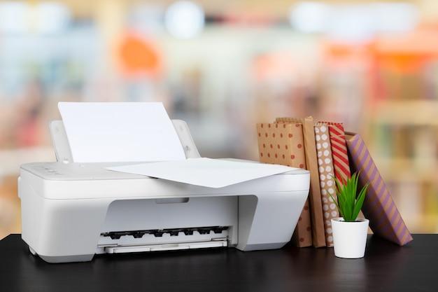 흐릿한 배경에 책이 있는 책상 위의 소형 홈 프린터
