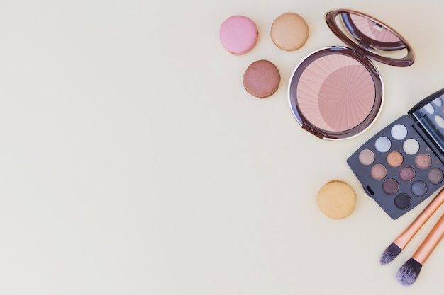 Compact powder; eyeshadow palette; makeup brush and macaroons on beige background