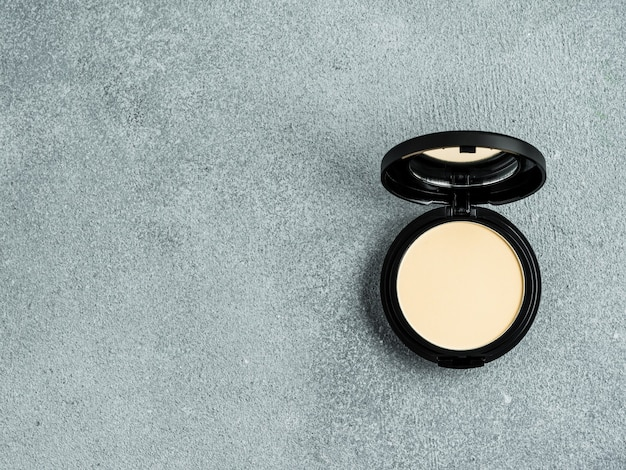 Compact powder on gray cement background. female pressed powder in opened black plastic case with mirror, copy space for text or design. top view or flat lay