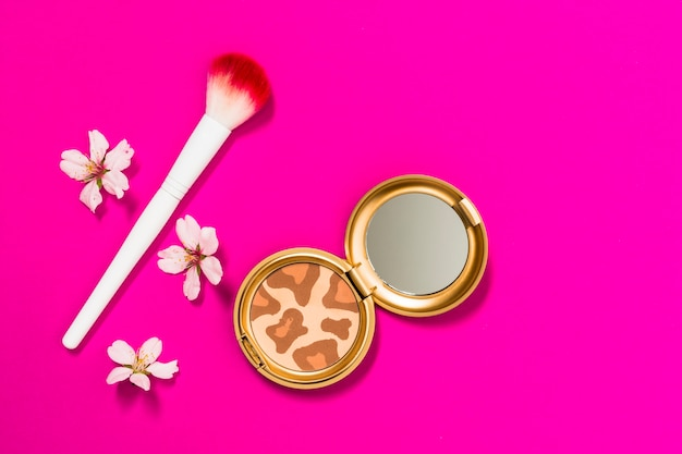 Compact powder palette with makeup brush and flowers on pink background
