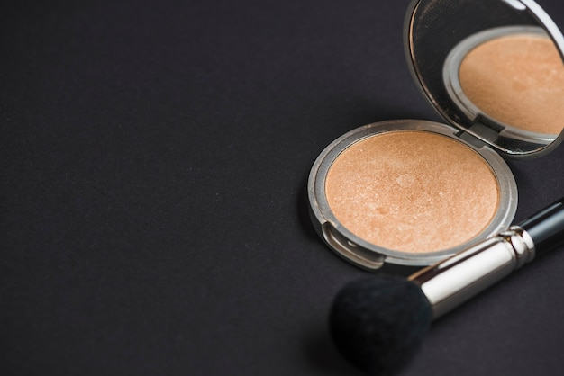 Compact powder with brush on black backdrop