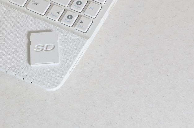 A compact sd memory card lies on a white netbook.