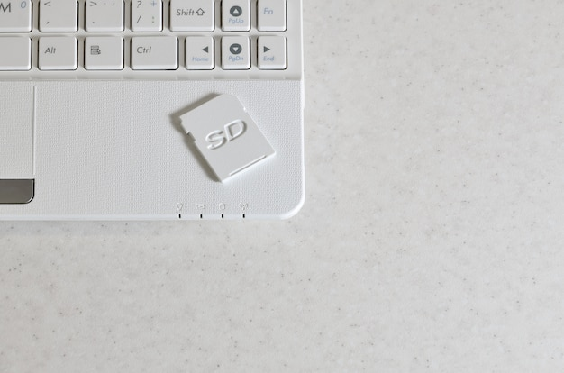 A compact sd memory card lies on a white netbook. the
