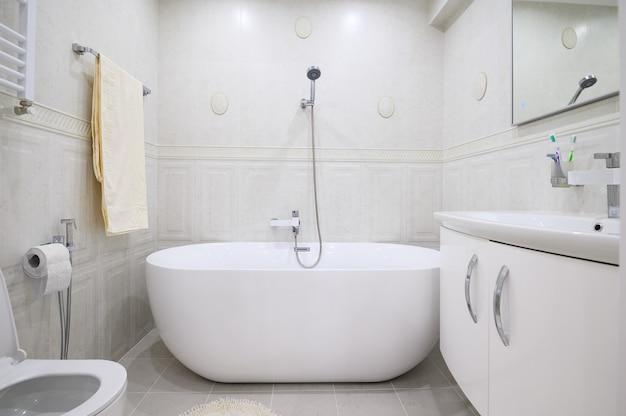 Компактная белая уютная ванная комната с ванной