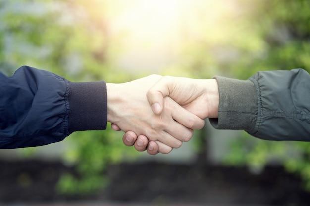 Товарищеские руки, сжимающие доверие успеха, уверенную концепцию. или крупный план деловой руки между двумя коллегами в парках.